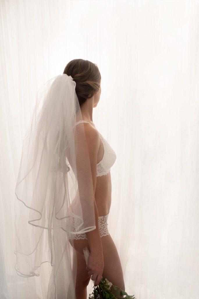 Boudoir und Portrait Fotografie am Tag der Hochzeit mit einer Braut in Unterwäsche mit einem Schleier